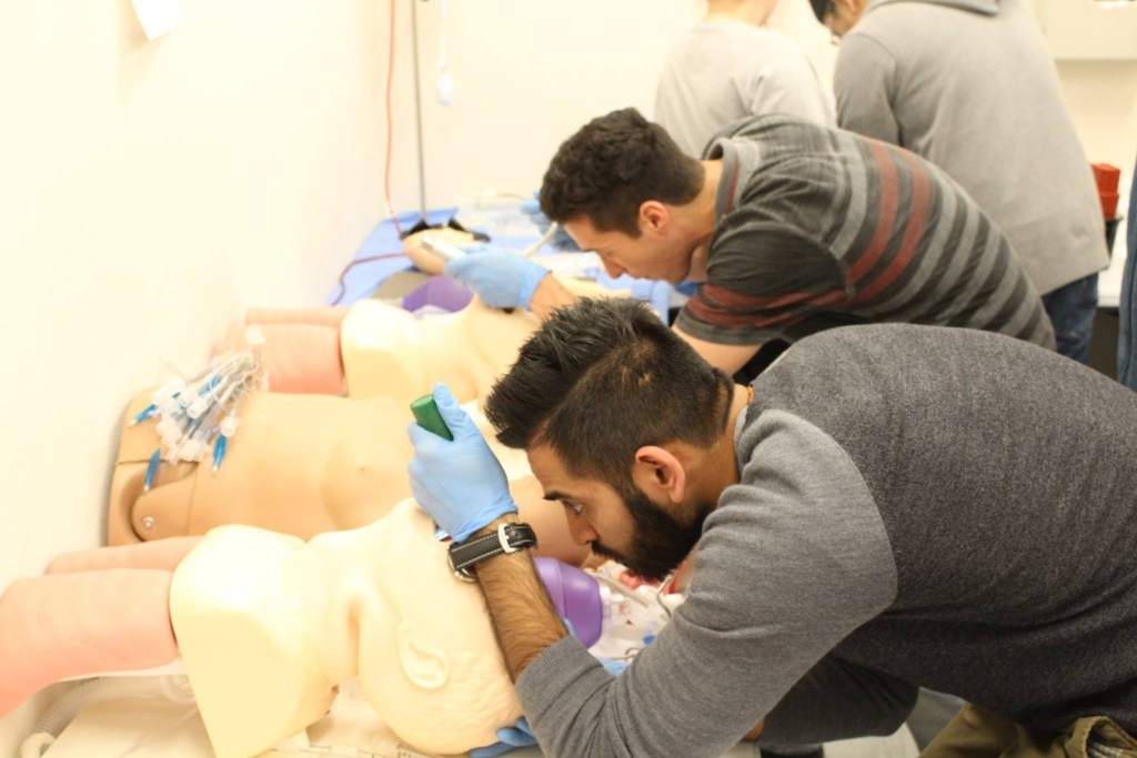 Saurin Patel and Benny Rossner practice intubation skills.