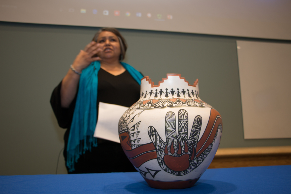 Seymour explains the meaning behind the symbols on the pot to the BCOM students, faculty, and staff.