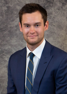 Portrait of Tyler Tumey in blue suit with gray background