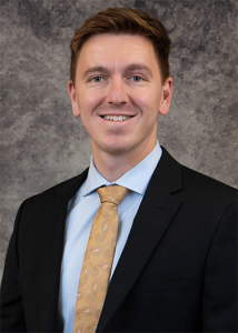 Portrait of Tyler Wilson in black suit with gray background